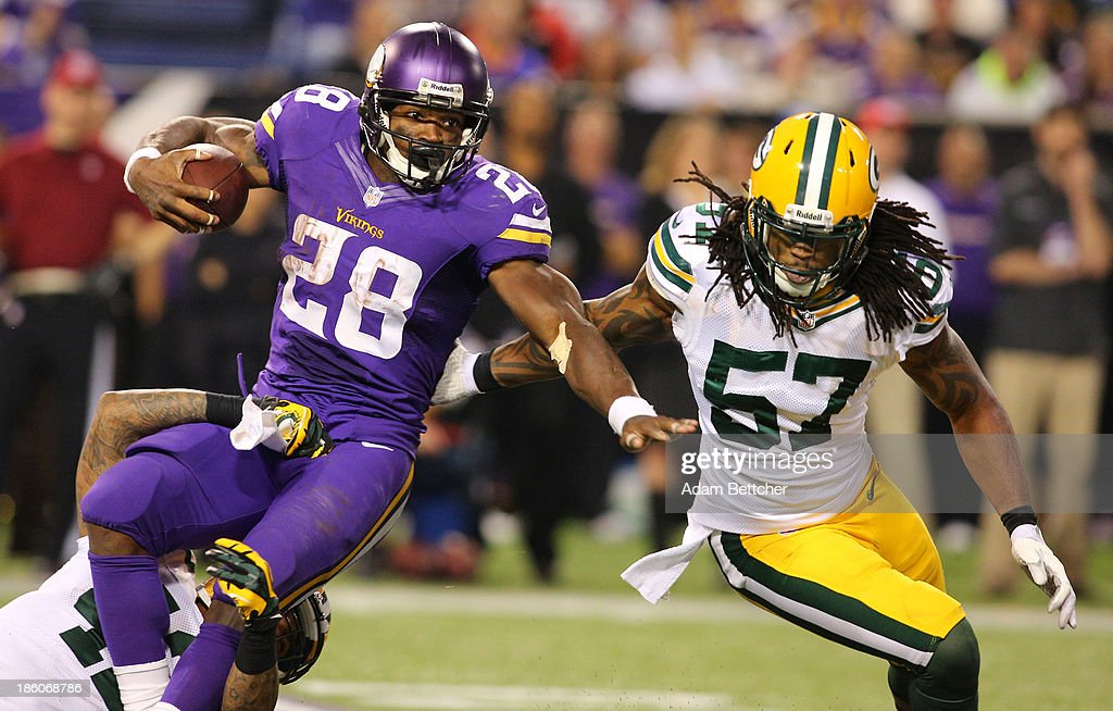 <a gi-track='captionPersonalityLinkClicked' href=/galleries/search?phrase=Adrian+Peterson+-+American+Football+Player+-+Minnesota+Vikings&family=editorial&specificpeople=210807 ng-click='$event.stopPropagation()'>Adrian Peterson</a> #28 of the Minnesota Vikings gets pulled down while <a gi-track='captionPersonalityLinkClicked' href=/galleries/search?phrase=Jamari+Lattimore&family=editorial&specificpeople=5532489 ng-click='$event.stopPropagation()'>Jamari Lattimore</a> #57 of the Green Bay Packers provides backup on October 27, 2013 at Mall of America Field at the Hubert Humphrey Metrodome in Minneapolis, Minnesota.