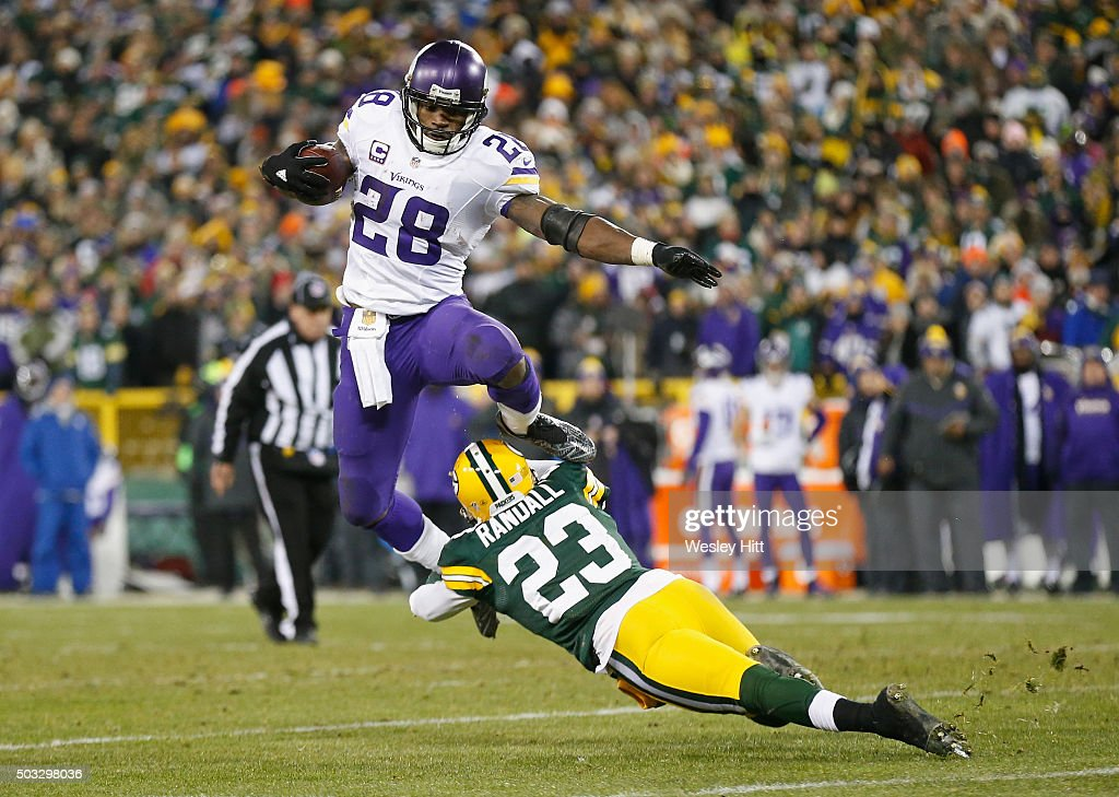 Adrian Peterson of the Minnesota Vikings hurdles Damarious Randall of the Green Bay Packers during the third quarter of their game at Lambeau Field...