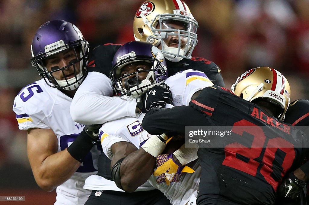 Adrian Peterson #28 of the Minnesota Vikings is hit by Aaron Lynch #59 and Kenneth Acker #20 of the San Francisco 49ers during their NFL game at Levi's Stadium on September 14, 2015 in Santa Clara, California.