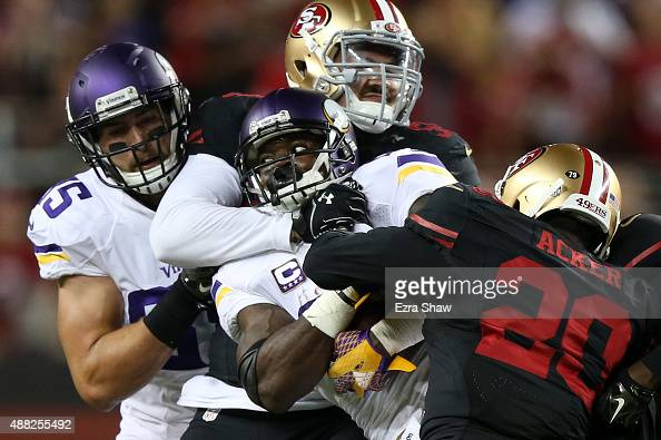 Adrian Peterson of the Minnesota Vikings is hit by Aaron Lynch and Kenneth Acker of the San Francisco 49ers during their NFL game at Levi's Stadium...