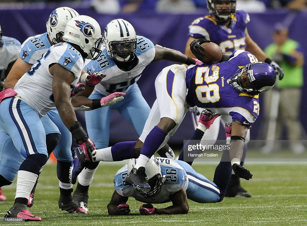 Adrian Peterson #28 of the Minnesota Vikings is tackled by Jordan Babineaux #26 of the Tennessee Titans during the third quarter of the game on October 7, 2012 at Mall of America Field at the Hubert H. Humphrey Metrodome in Minneapolis, Minnesota. The Vikings defeated the Titans 30-7.