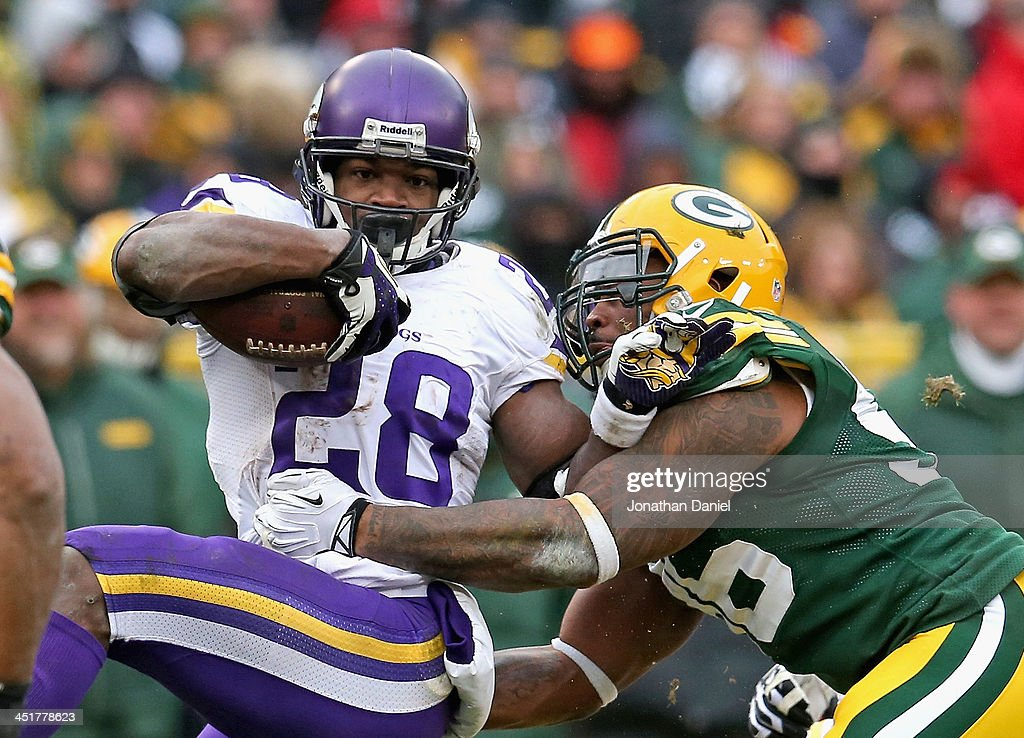 <a gi-track='captionPersonalityLinkClicked' href=/galleries/search?phrase=Adrian+Peterson+-+American+Football+Player+-+Minnesota+Vikings&family=editorial&specificpeople=210807 ng-click='$event.stopPropagation()'>Adrian Peterson</a> #28 of the Minnesota Vikings is tackled by Mike Neal #96 of tyhe Green Bay Packers at Lambeau Field on November 24, 2013 in Green Bay, Wisconsin. The Vikings and the Packers tied 26-26 after overtime.