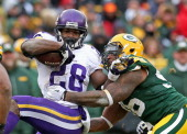 Adrian Peterson of the Minnesota Vikings is tackled by Mike Neal of tyhe Green Bay Packers at Lambeau Field on November 24 2013 in Green Bay...