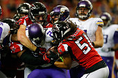 Adrian Peterson of the Minnesota Vikings is tackled by Philip Wheeler and Kroy Biermann of the Atlanta Falcons during the second half at the Georgia...