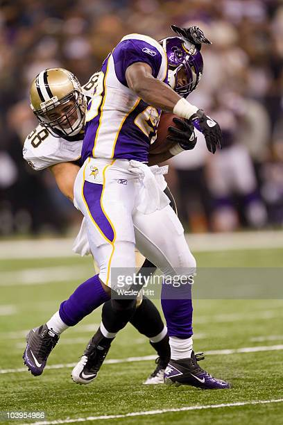Adrian Peterson of the Minnesota Vikings is tackled by Scott Shanle of the New Orleans Saints at the Louisiana Superdome on September 9 2010 in New...
