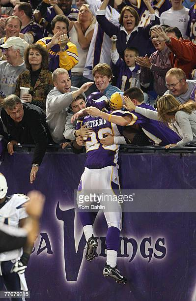 Adrian Peterson of the Minnesota Vikings jumps into the stands following a touchdown during an NFL game against the San Diego Chargers at the Hubert...