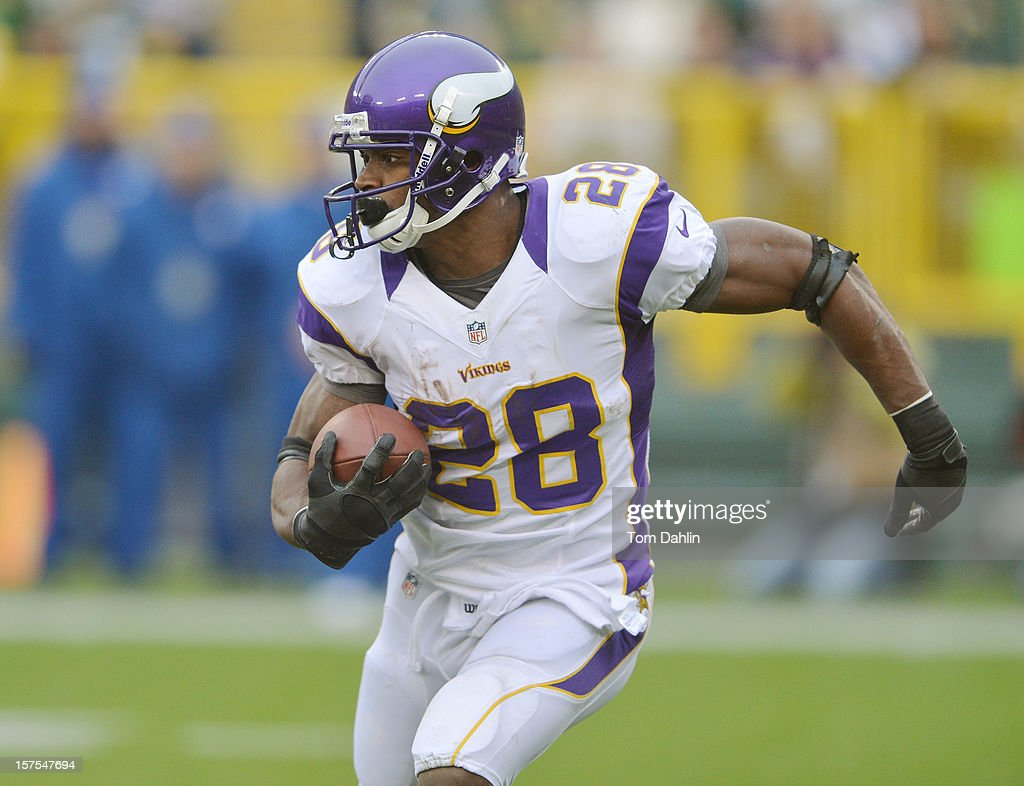 Adrian Peterson #28 of the Minnesota Vikings passes the ball during an NFL game against the Green Bay Packers at Lambeau Field on December 2, 2012 in Green Bay, Wisconsin.