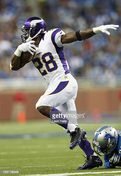Adrian Peterson of the Minnesota Vikings runs for a first down as Ricardo Silva of the Detroit Lions attempts to make the stop during the game at...