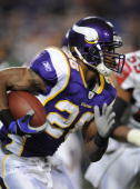 Adrian Peterson of the Minnesota Vikings runs with the ball during an NFL game against the Atlanta Falcons at the Hubert H Humphrey Metrodome on...
