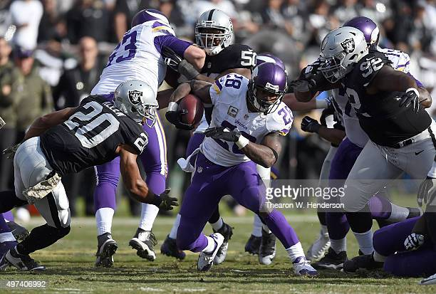 Adrian Peterson of the Minnesota Vikings rushes with the ball against the Oakland Raiders during the second quarter of an NFL football game at Oco...