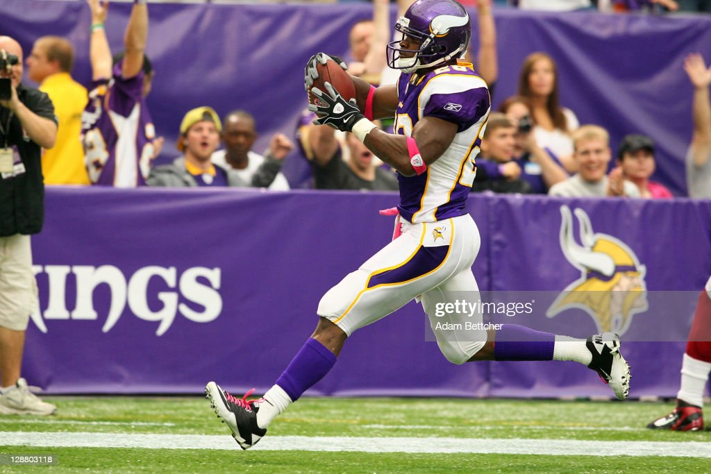 Adrian Peterson of the Minnesota Vikings scores a touchdown against the Arizona Cardinals at the Hubert H Humphrey Metrodome on October 9 2011 in...