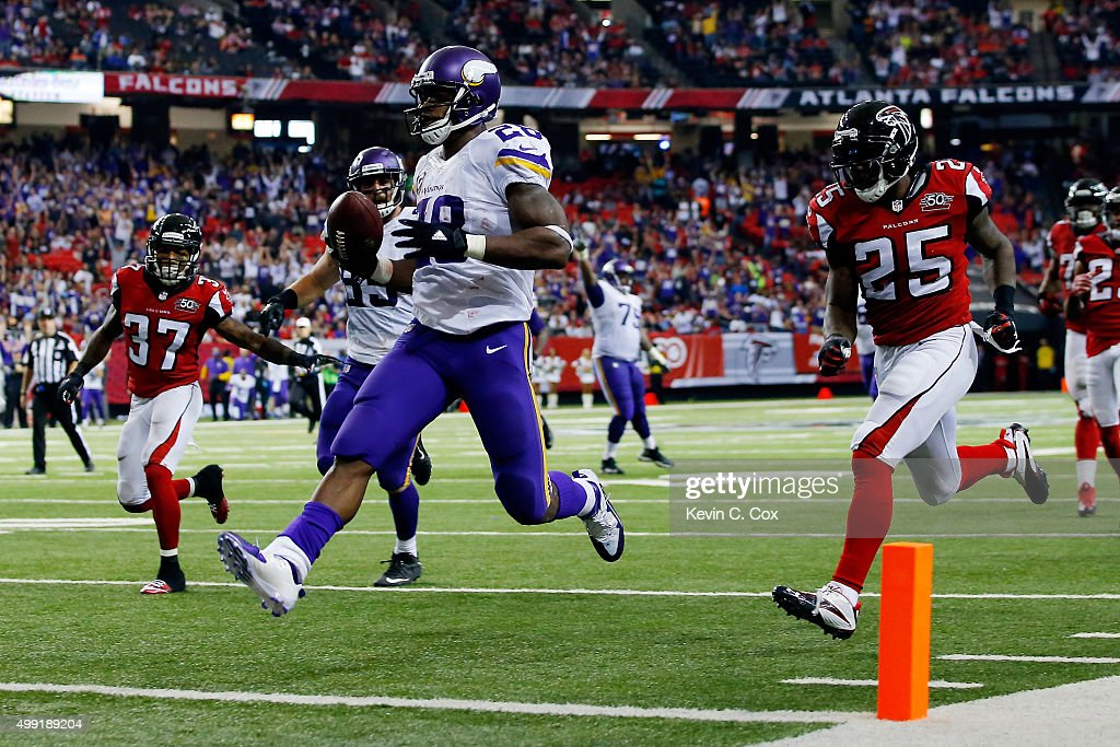 Adrian Peterson of the Minnesota Vikings scores a touchdown during the second half against the Atlanta Falcons at the Georgia Dome on November 29...