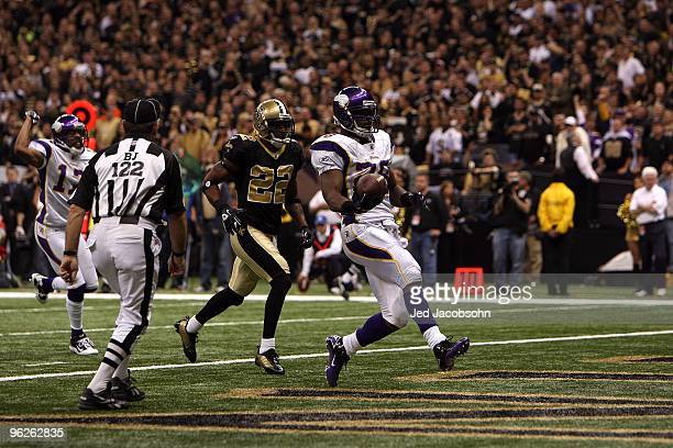 Adrian Peterson of the Minnesota Vikings scores a touchdown in the first quarter against Tracy Porter and the New Orleans Saints during the NFC...