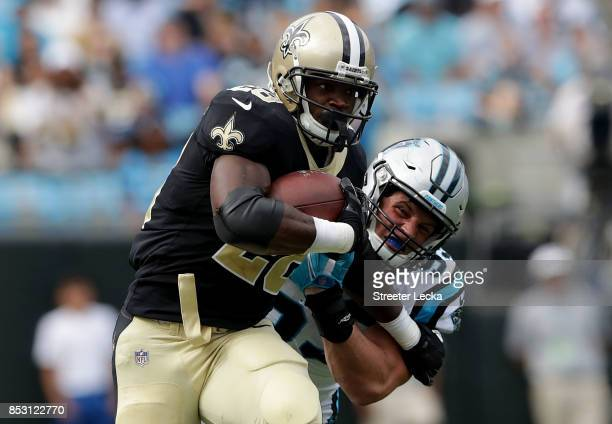 Adrian Peterson of the New Orleans Saints runs with the ball against Luke Kuechly of the Carolina Panthers during their game at Bank of America...