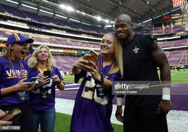 Adrian Peterson of the New Orleans Saints signs autographs and takes pictures with fans before the game against the Minnesota Vikings on September 11...