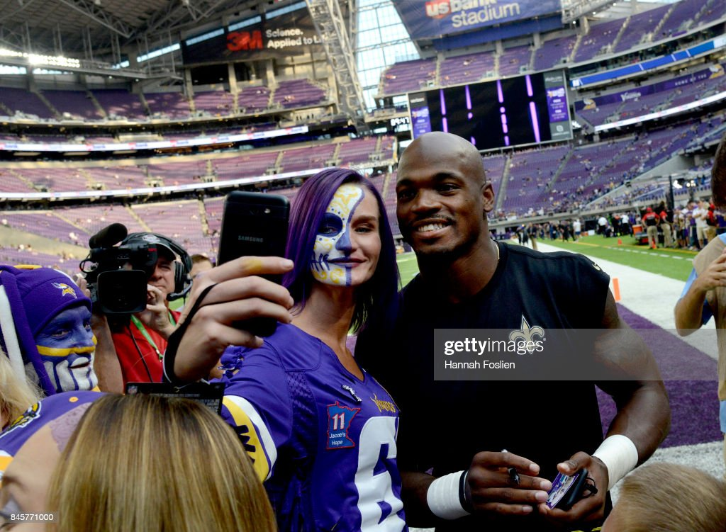 Adrian Peterson #28 of the New Orleans Saints signs autographs and takes pictures with fans before the game against the Minnesota Vikings on September 11, 2017 at U.S. Bank Stadium in Minneapolis, Minnesota. Peterson returns to Minnesota for the first time since joining the Saints this offseason.