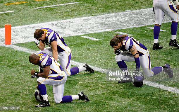 Adrian Peterson Ryan D'Imperio and Brian Robison of the Minnesota Vikings take a moment before the game against the New Orleans Saints on December 18...