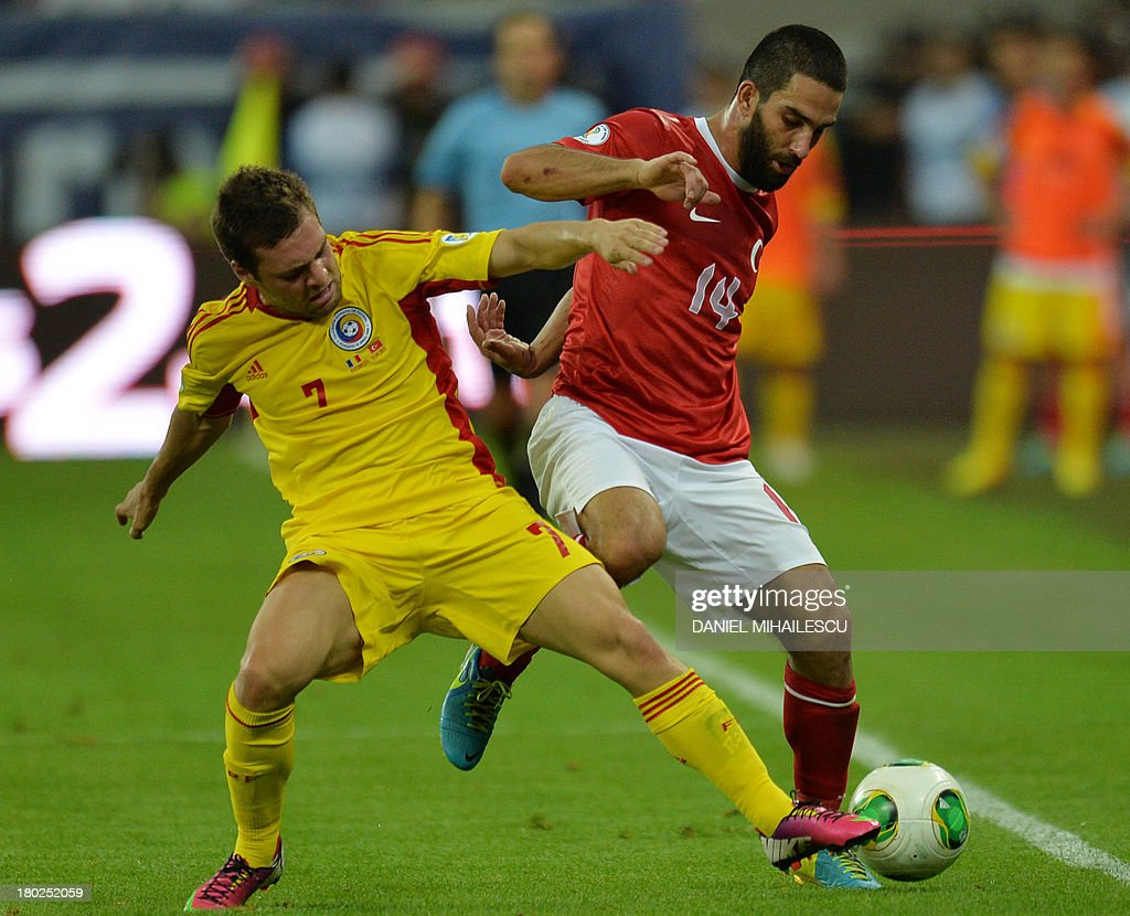 Adrian Popa (L) of Romania vies for the ball with Arda Turan (R) of Turkey the FIFA World Cup 2014 qualifying football match Romania vs Turkey in Bucharest on September 10, 2013. AFP PHOTO / DANIEL MIHAILESCU