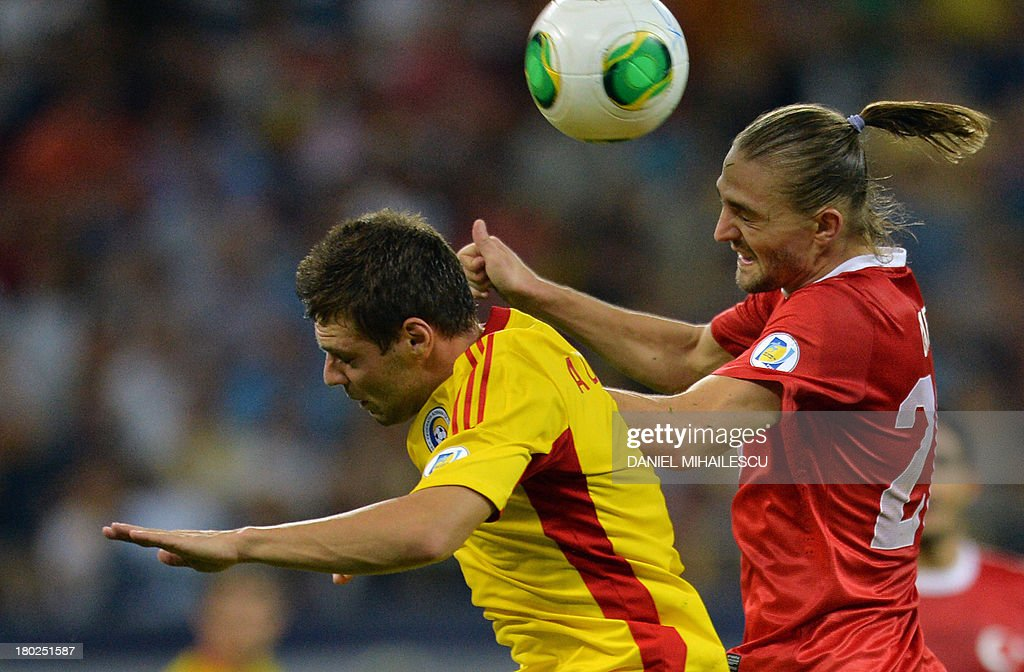 Adrian Popa (L) of Romania vies for the ball with Caner Erkin (R) of Turkey during the FIFA World Cup 2014 qualifying football match Romania vs Turkey in Bucharest on September 10, 2013. AFP PHOTO / DANIEL MIHAILESCU
