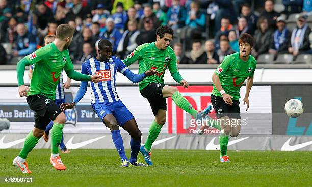 Adrian Ramos of Berlin is challenged by Andre Hoffmann Manuel Schmiedebach and Hiroki Sakai of Hannover during the Bundesliga match between Hertha...