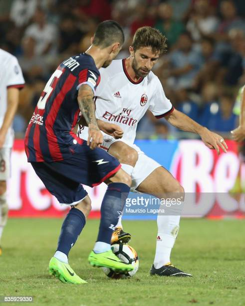 Adrian Stoian of Crotone competes for the ball with Fabio Borini of Milan during the Serie A match between FC Crotone and AC Milan on August 20 2017...