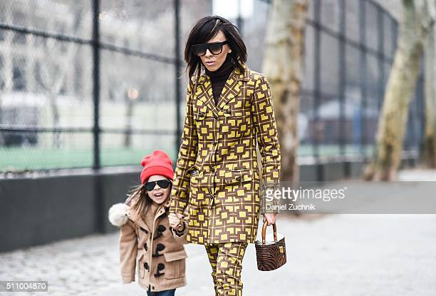Adriana Kubieniec is seen with her son outside the DKNY show wearing Adriana Kubieniec ADartist coat and pants Celine sunglasses and wood art bag...