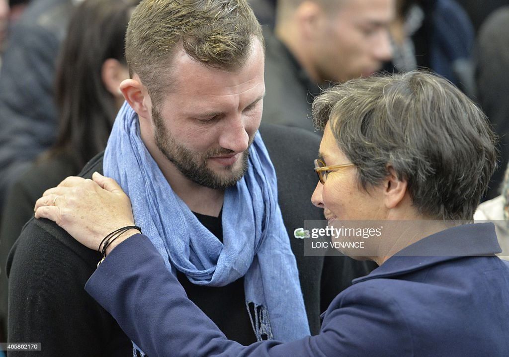 Adriani Vastine, brother of late Olympic boxer Alexis Vastine, talks with French former Sport minister Valerie Fourneyron (R) on March 11, 2015 at the Insep national Sport Institute in Vincennes, outside Paris, during a ceremony in memory of Olympic champion swimmer Camille Muffat, yachtswoman Florence Arthaud and Olympic boxer Alexis Vastine who died two day before with five French TV crew members and two Argentine pilots in the crash of helicopters in Argentina. AFP PHOTO / LOIC VENANCE