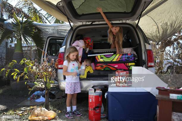 Adrianna Dworniczak and her sister Ariella Dworniczak wait at the back of their mother's van as she begins the process of salvaging what she can from...