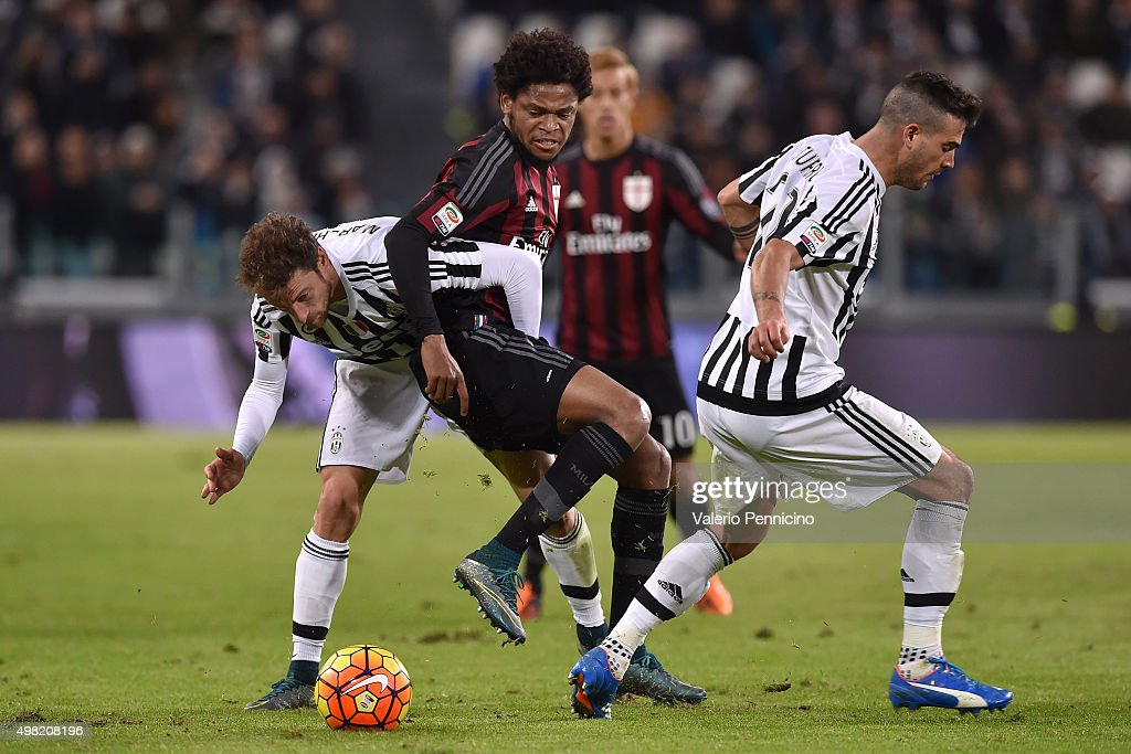 Adriano (C) of AC Milan is challenged by Claudio Marchisio (L) and Stefano Sturaro of Juventus FC during the Serie A match between Juventus FC and AC Milan at Juventus Arena on November 21, 2015 in Turin, Italy.