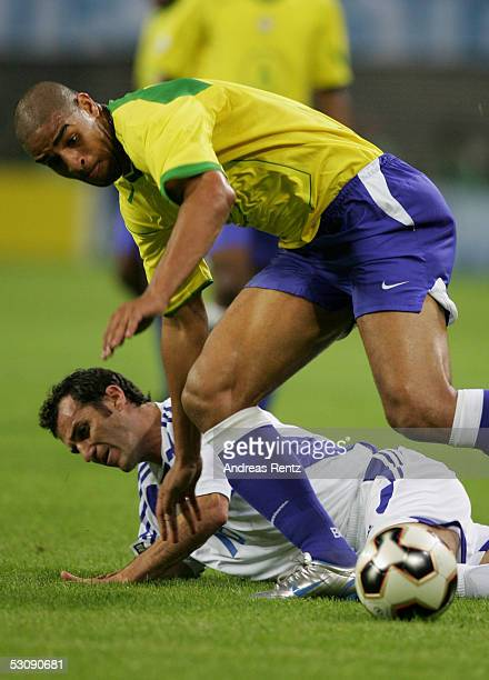 Adriano of Brazil challenges with Ioannis Goumas of Greece during the FIFA Confederations Cup 2005 match between Brazil and Greece on June 16 2005 in...