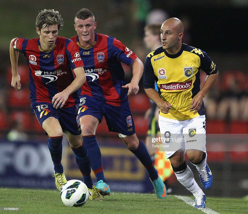 Adriano Pellegrino of the Mariners controls the ball in front of Craig Goodwin pf the Jets during the round ten A-League match between the Newcastle Jets and the Central Coast Mariners at Hunter Stadium on December 8, 2012 in Newcastle, Australia.