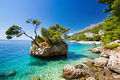 Small rocky formation in the water of Adriatic sea in tourist resort of Brela