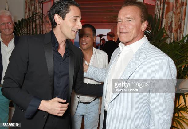 Adrien Brody and Arnold Schwarzenegger attend The 9th Annual Filmmakers Dinner hosted by Charles Finch and JaegerLeCoultre at Hotel du CapEdenRoc on...