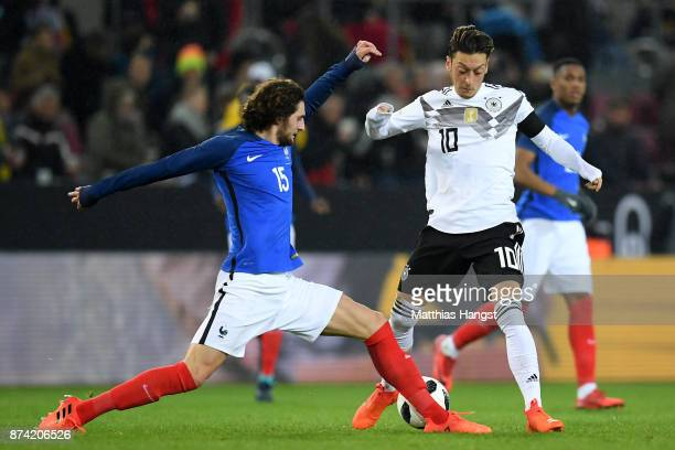 Adrien Rabiot of France and Mesut Ozil of Germany battle for possession during the international friendly match between Germany and France at...
