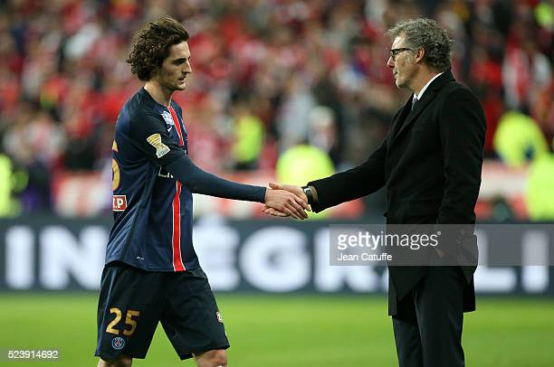 Adrien Rabiot of PSG shakes hands with coach of PSG Laurent Blanc when he leaves the field after receiving a red card during the French League Cup...