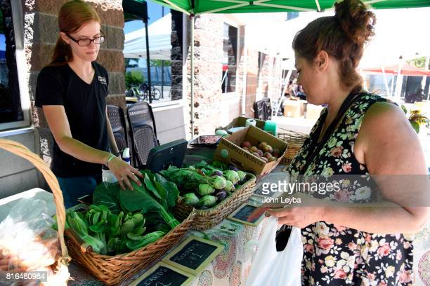 Adrien SchlessMeier with the Denver Botanic Garden points out the fresh collard greens to Jasmine Pamphilis at the Farmer's market at the DHS Richard...