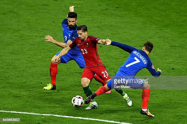 Adrien Silva of Portugal takes on Olivier Giroud and Antoine Griezmann of France during the UEFA EURO 2016 Final match between Portugal and France at...