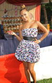 Adrienne Bailon poses in front of the Ring Toss at the Absolut Brooklyn BBQ at The Estate on July 17 2010 in Sag Harbor New York