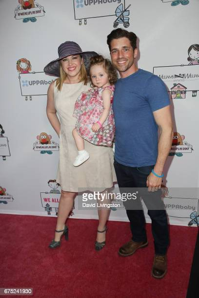 Adrienne Frantz Amelie Irene Bailey and Scott Bailey attends the WE ALL PLAY FUNdraiser hosted by the Zimmer Children's Museum at the Zimmer...