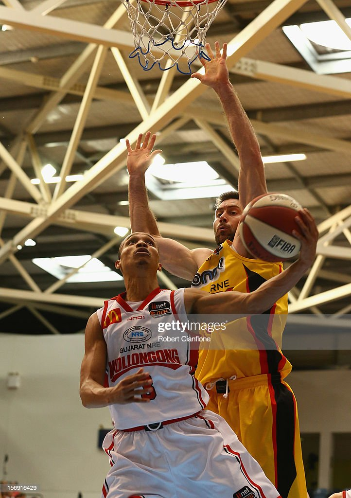 Adris Deleon of the Hawks attempts to score as Christopher Goulding of the Tigers attempts to block during the round eight NBL match between the Melbourne Tigers and the Wollongong Hawks at State Netball Hockey Centre on November 25, 2012 in Melbourne, Australia.