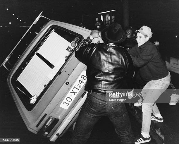 AdRock member of the band 'Beastie Boys' tipping a car over with a group of guys Switzerland circa 1987