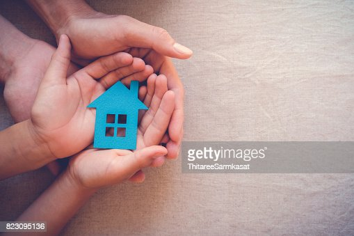 Adult and child hands holding paper house, family home and real estate concept : Stock Photo