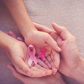 Adult and child hands holding pink ribbons, Breast cancer awareness, abdominal cancer awareness and October Pink