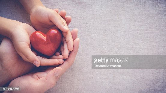 adult and child hands holding red heart, health care love and family concept : Stock Photo