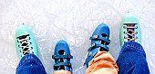 Adult and child ice skates standing on ice