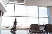 Pilot is walking through terminal near glass wall. He carrying suitcase and holding coffee. Panoramic view. Copy space on right side