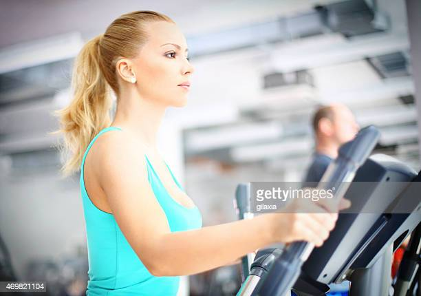 Adult blond woman exercising on treadmill.