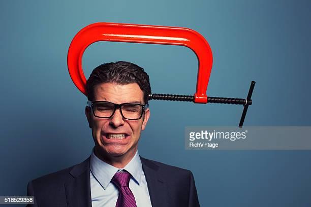 Hombre de negocios adulto de dolor en torno a la cabeza