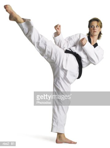 adult caucasian female martial arts expert in white with blackbelt performs roundhouse kick to right : Stock Photo