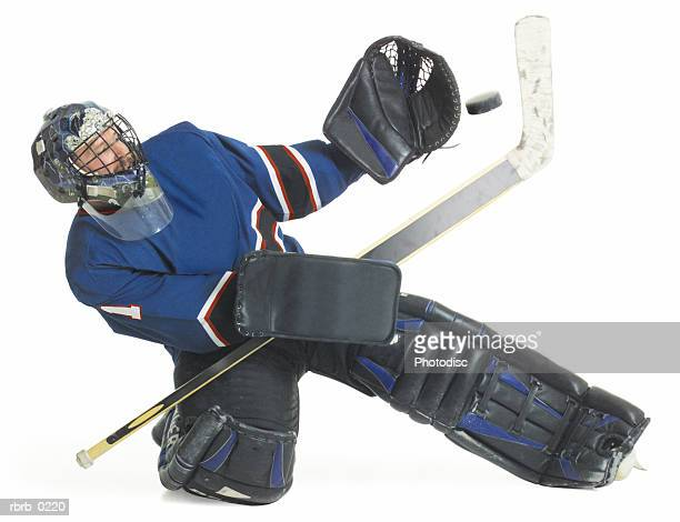 adult caucasian male hockey goalie kneels down and raises his arm to block a puck flying towards him